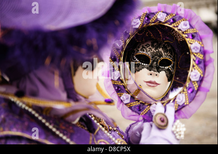 A woman wearing a traditional Carnival costume reflected in her own mirror, Venice, Italy. - Stock Photo