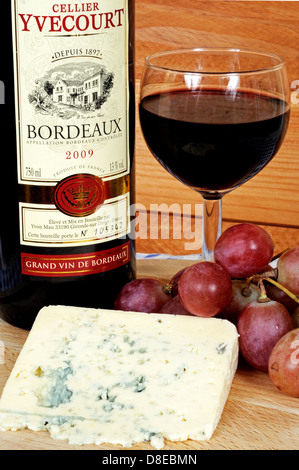 Bleu d'Auvergne cheese, red wine and red grapes on a wooden cheese board. - Stock Photo