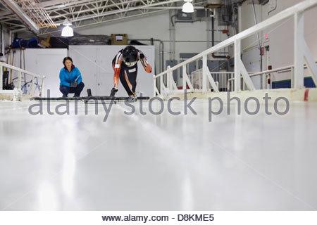 Female skeleton athlete with coach practicing on track - Stock Photo