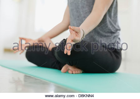 Woman sitting in lotus position in yoga studio - Stock Photo
