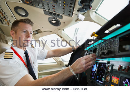 Male pilot checking control panel in airplane cockpit - Stock Photo