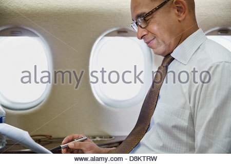 Businessman reading documents in airplane - Stock Photo