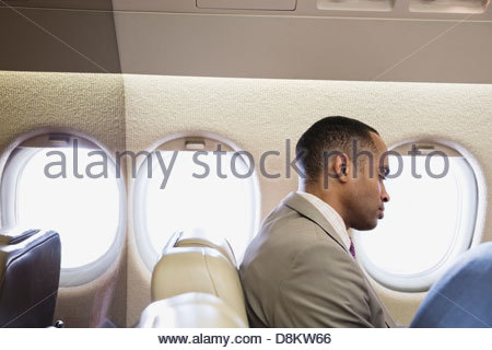 Businessman traveling in airplane - Stock Photo