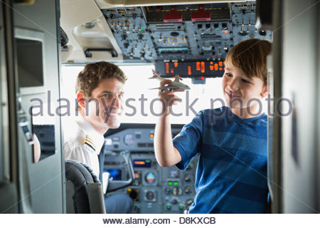 Boy playing with toy plane in airplane cockpit - Stock Photo