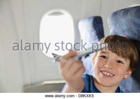 Boy playing with toy plane in airplane - Stockfoto