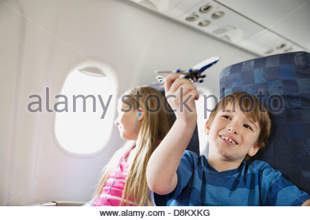 Boy playing with toy plane while sister listens to music in airplane - Stock Photo