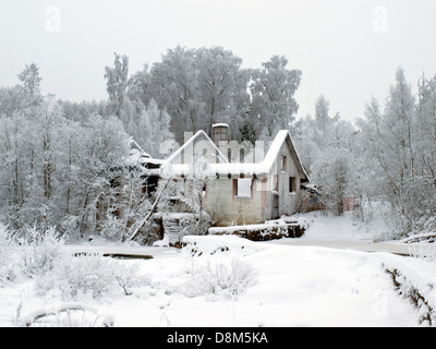 Old burnt house on winter river. - Stock Photo