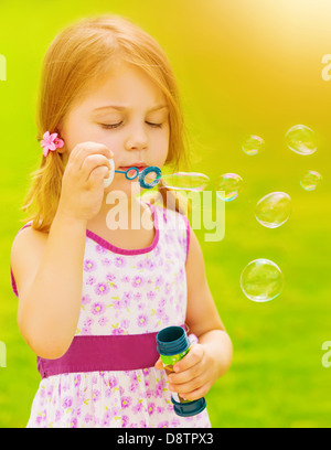Closeup portrait of cute baby girl blowing soap bubbles outdoors, playing game on spring garden, sunny day, happy - Stock Photo