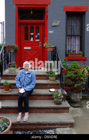 senior woman sitting on house steps - Stockfoto