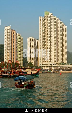 Sampan boat in the Aberdeen Harbour, skyscrapers overlooking the Aberdeen Channel, Aberdeen, Hong Kong - Stock Photo