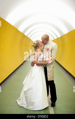 Bride and groom kissing in subway - Stock Photo
