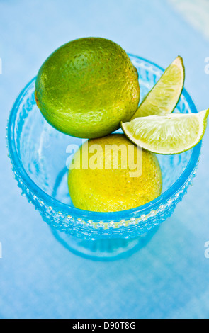 Close up of lime and lemon in blue bowl - Stockfoto