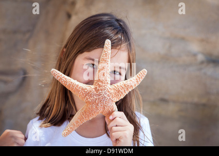 Young Pretty Girl Playing with Starfish. - Stock Photo