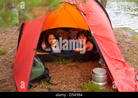 Two female tourists lying in tent - Stock Photo