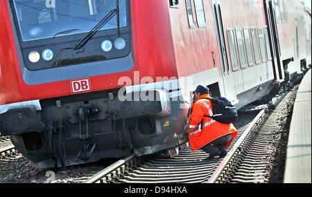 Staff of the Deutsche Bahn examine the damages of a derailed train in Schkeuditz, Germany, 11 June 2013. A regional - Stock Photo