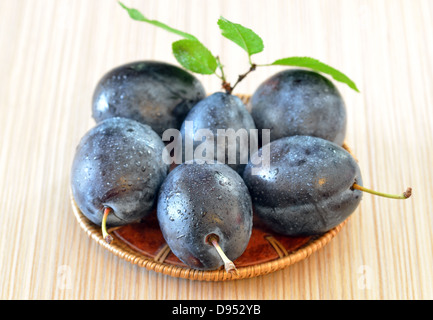 Rip plums on basket on wooden table - Stockfoto