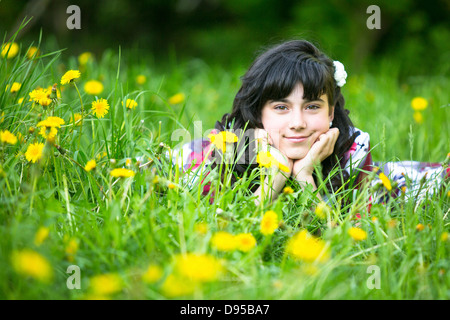 Portrait of a teen girl lying in the grass - Stock Photo
