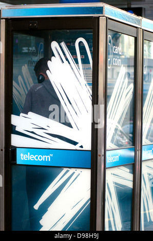 Man talks in a street Telecom telephone payphone booth, New Zealand - Stock Photo