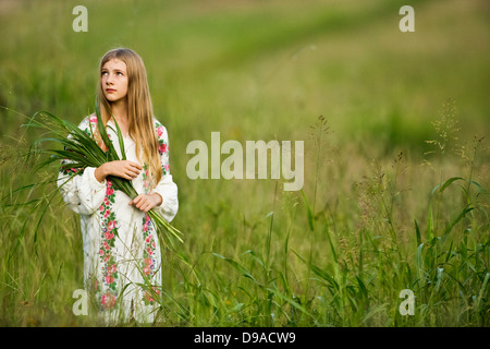 Young girl gathering wild grasses in summer field, wearing traditional Russian costume - Stock Photo