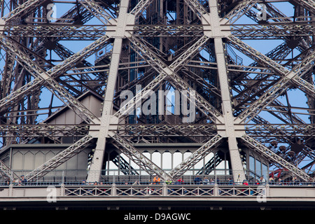 Tourists looking out from first level platform of Eiffel Tower beneath complex lattice ironwork - Stock Photo