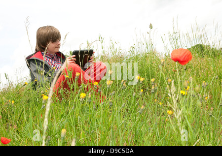 young male boy using ipad mini tablet computer - Stock Photo