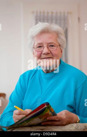 Germany, Berlin, Portrait of senior woman doing crossword, smiling - Stockfoto