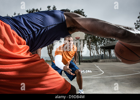 Young basketball players playing on court, close up - Stock Photo