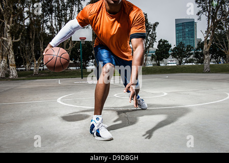 Young man playing basketball on court, close up - Stock Photo