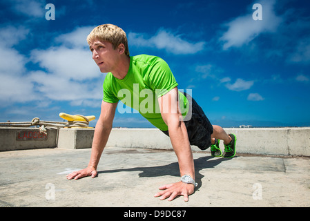 Young man performing push ups on pier - Stock Photo
