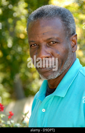 Happy mature man looking relaxed in garden, vertical composition - Stock Photo