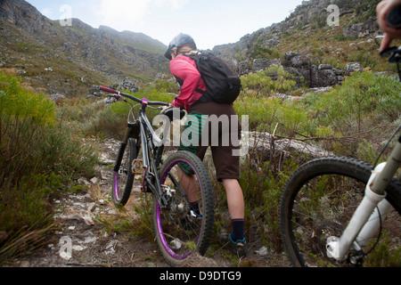 Young woman pushing mountain bike up mountain path - Stock Photo