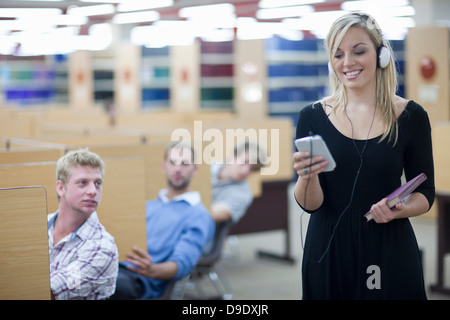 Three male students watching female student - Stock Photo