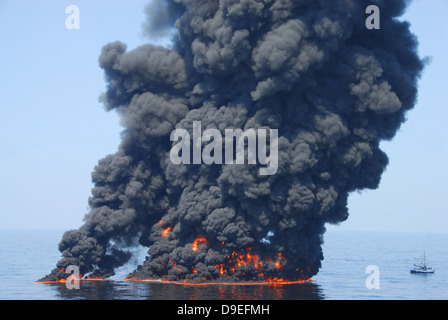 Dark clouds of smoke and fire emerge as oil burns during a controlled fire in the Gulf of Mexico. - Stock Photo