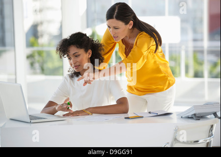 Two female friends reviewing bill on a laptop at home - Stock Photo