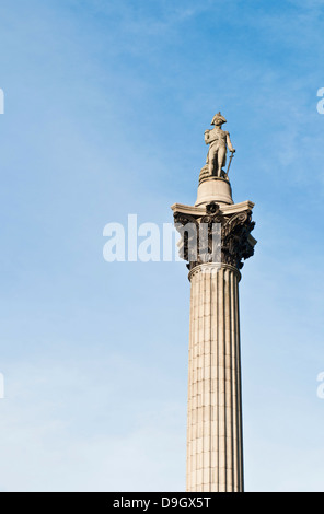 Nelson's Column monument in Trafalgar Square, London, England (against a blue sky) - Stock Photo