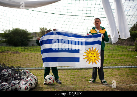A portrait two young school kids holding Uruguay flag H P Williams schools football grounds in Stompneus Bay in - Stockfoto