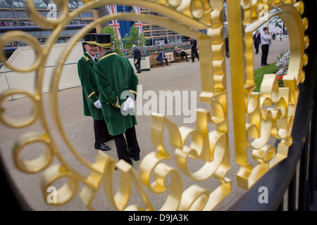 Official Gatekeepers seen through the crown design at the entrance during the annual Royal Ascot horseracing festival - Stock Photo