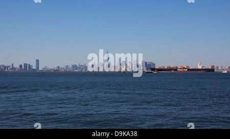 NEW YORK, NY, USA - MAY 27, 2013: A German container ship arrives at New York City before the backdrop of the Manhattan - Stock Photo