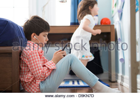 Boy playing on smartphone in playground - Stock Photo