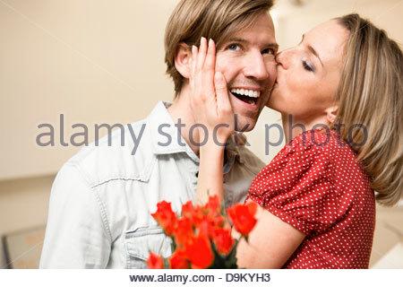Woman kissing man on cheek - Stock Photo