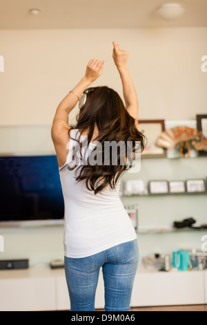 Mid adult woman wearing headphones and dancing, rear view - Stock Photo