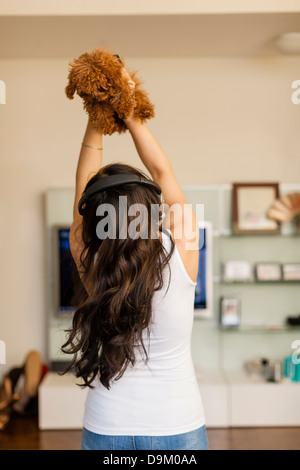 Mid adult woman wearing headphones and dancing with dog - Stock Photo