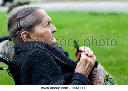 Close-up of a senior woman sitting on a wheelchair - Stock Photo