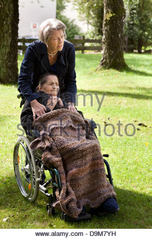 Daughter pushing her old disabled mother on a wheelchair in a garden - Stock Photo