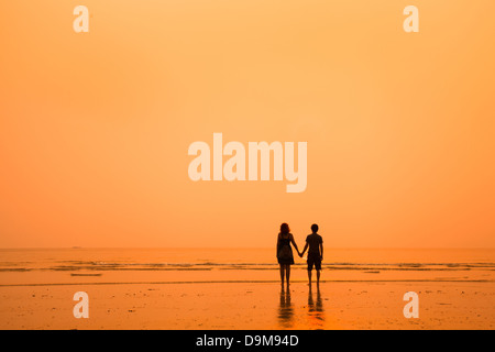 sunset silhouettes of loving couple on the beach - Stock Photo