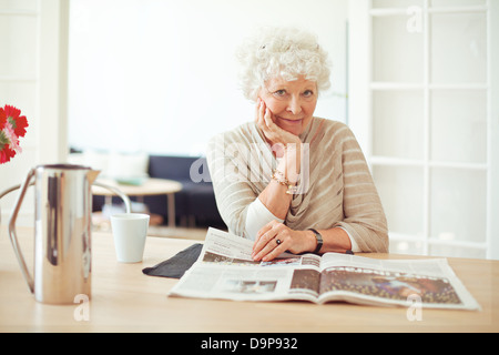 Portrait of a stylish old woman at home reading a magazine - Stock Photo