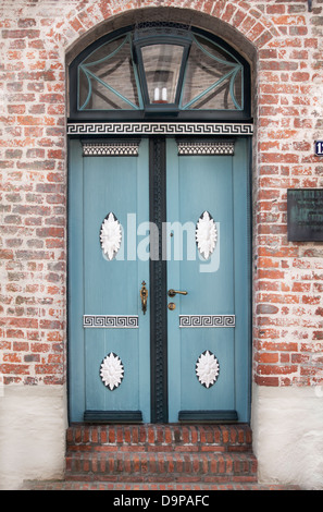 Beautiful blue wooden door with ornaments framed in a redbricked wall - Stock Photo