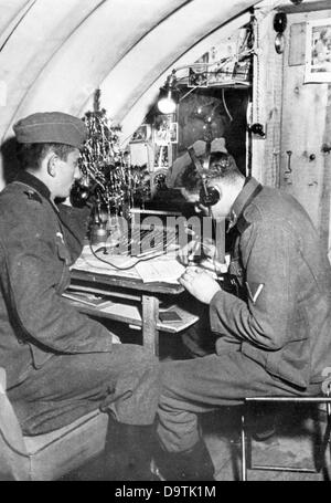 Soldiers of the German Wehrmacht are pictured at work at the radio on Christmas 1940. The Nazi Propaganda! on the - Stock Photo