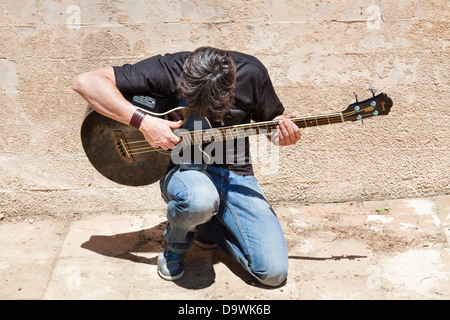 young man playing acoustic guitar kneeling outside - Stock Photo