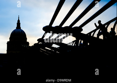 Dramatic back lit view of Saint Paul's Cathedral and the Millennium Bridge over the River Thames, In London, England, - Stock Photo